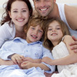 Portrait of parents and children lying in bed — Stock Photo