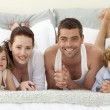 Portrait of happy family lying in bed — Stock Photo