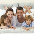 Happy family lying in bed and smiling at the camera — Stock Photo #10298376