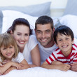 Family lying in bed together — Stock Photo