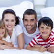 Portrait of family lying in bed together - Stock Photo