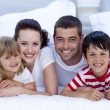 Smiling family lying in bed together — Stock Photo