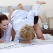 Son playing with his parents in bed — Stock Photo