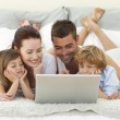 Royalty-Free Stock Photo: Family in bed using a laptop