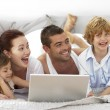 Happy family in bed using a laptop — Stock Photo