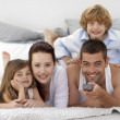 Family lying in bed and using a remote — Stock Photo #10298408