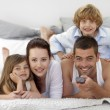 Family lying in bed and using a remote — Stock Photo