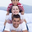 Stock Photo: Happy parents and son playing in bed