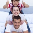 Happy parents and son in bed with thumbs up — Stock Photo #10298428