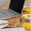 Laptop on a kitchen table. Working having breakfast — Stock Photo