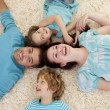 Stock Photo: Smiling family on floor with heads together