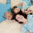Stock Photo: Parents and daughter on floor with heads together