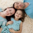 Stock Photo: Portrait of parents and daughter on floor with heads together