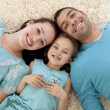 High angle of parents and daughter on floor with heads together — Stock Photo #10298486