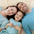 High angle of parents and daughter on floor with heads together — Stock Photo