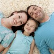 Smiling parents and girl on floor with heads together — Stock Photo #10298490