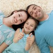 Parents and little girl on floor with thumbs up — Stock Photo