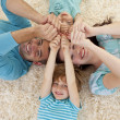 Happy family on floor with heads and hands together — Stock Photo #10298502