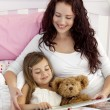 Stock Photo: Mother and daughter reading in bed