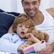 Father and son reading a book in bed — Stock Photo