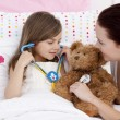 Mother and daughter playing doctors in bed — Stock Photo