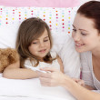 Mother taking her daughter's temperature — Stock Photo