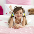 Little girl on headphones listening to the music in bed — Stock Photo #10298558