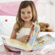 Beautiful little girl reading in bed — Stock Photo