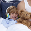 Stock Photo: Boy listening to music in bedroom