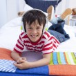 Stock Photo: Portrait of boy on headphones listening to music in bed