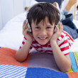 Stock Photo: Smiling boy listening to music in bed with headphones on