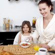 Little girl having breakfast with her mother — Stock Photo