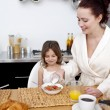 Foto Stock: Daughter and mother having breakfast