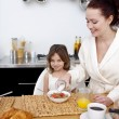 Daughter and mother in breakfast time — Stock Photo