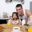 Daughter eating cereals and fruit in kitchen — Stock Photo