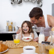 Stock Photo: Daughter eating cereals and fruit for breakfast