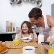 Little girl enjoying her breakfast with her father - Stock Photo
