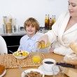 Kid having breakfast with his mother - Stock Photo