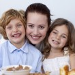 Portrait of children having breakfast with their mother — Stock Photo