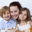 Children having breakfast with their mother - Stock Photo