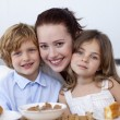 Children and mother having breakfast - Stock Photo