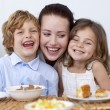 Children having breakfast with their mother — Stock Photo #10298617