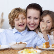 Children and mother having fun in breakfast — Stock Photo