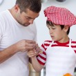 Stock Photo: Boy hurt his finger and father treating it