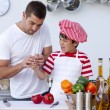 Stock Photo: Boy cut his finger in kitchen and father treating it