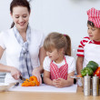 Mother and children cutting vegetables in kitchen — Stock Photo