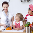 Mother and children cutting peppers in kitchen — Stock Photo