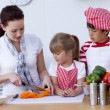 Children helping mother cooking in kitchen — Stockfoto #10298643