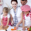 Happy family preparing a salad in kitchen — Stock Photo #10298649