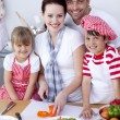 Young family cutting vegetables in kitchen — Stock Photo #10298650
